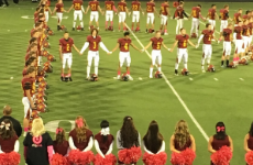 Prairie High School football player holds hand up during National Anthem